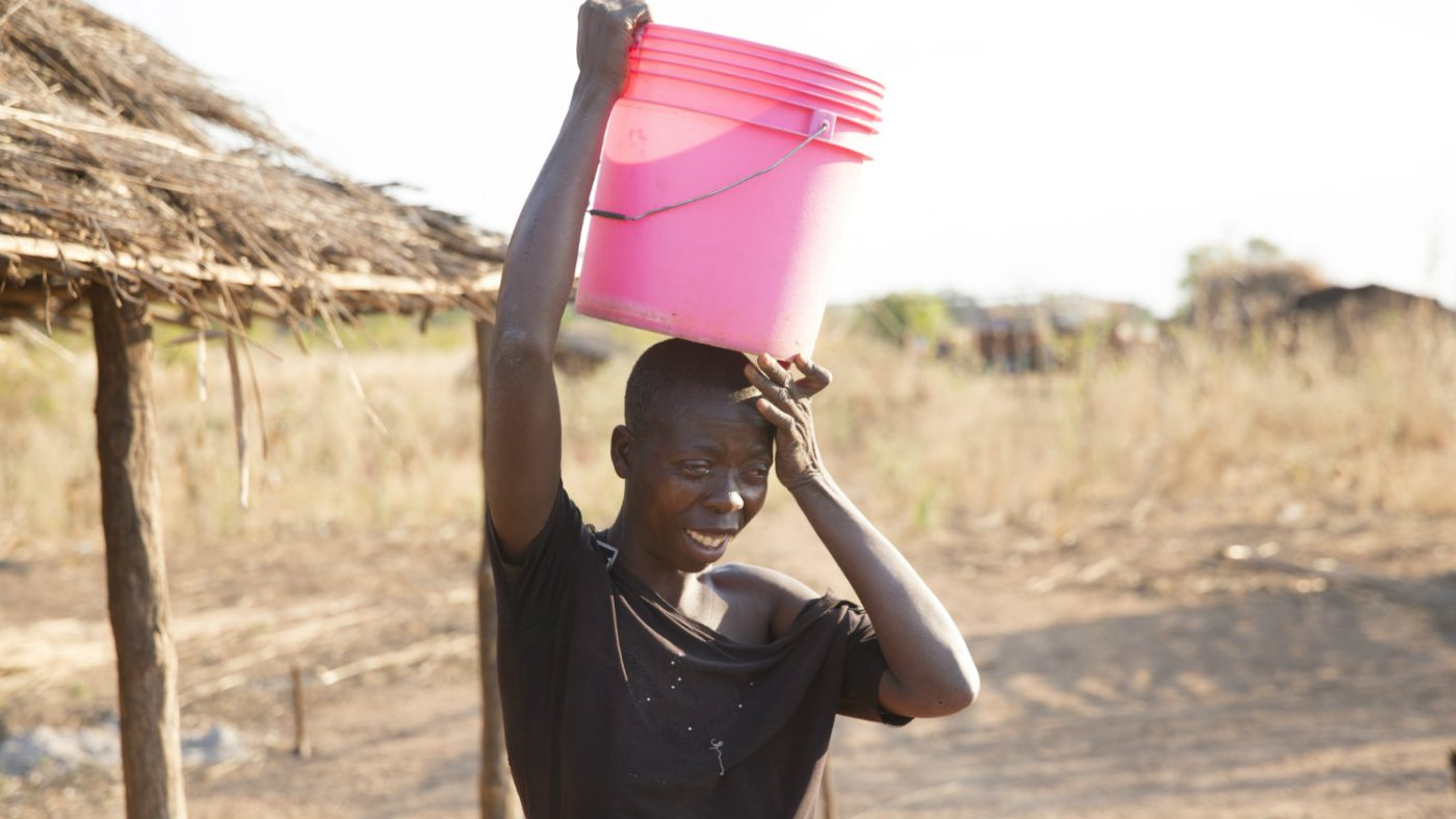 Laurinda carries a bucket to fetch water.