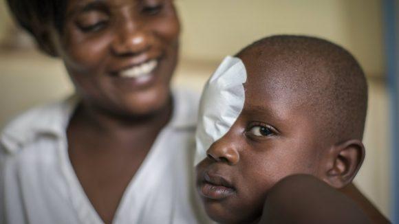 Un bambino con la benda sull'occhio guarda davanti a sè. Dietro di lui una donna sorride mentre lo guarda con tenerezza.