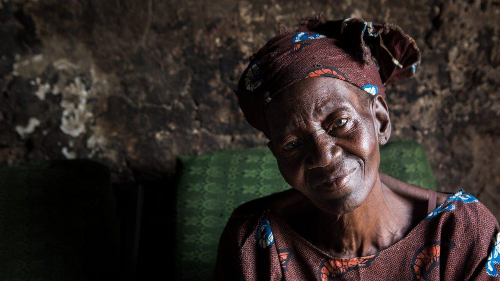 Una donna anziana sorride e guarda di fronte a sè.