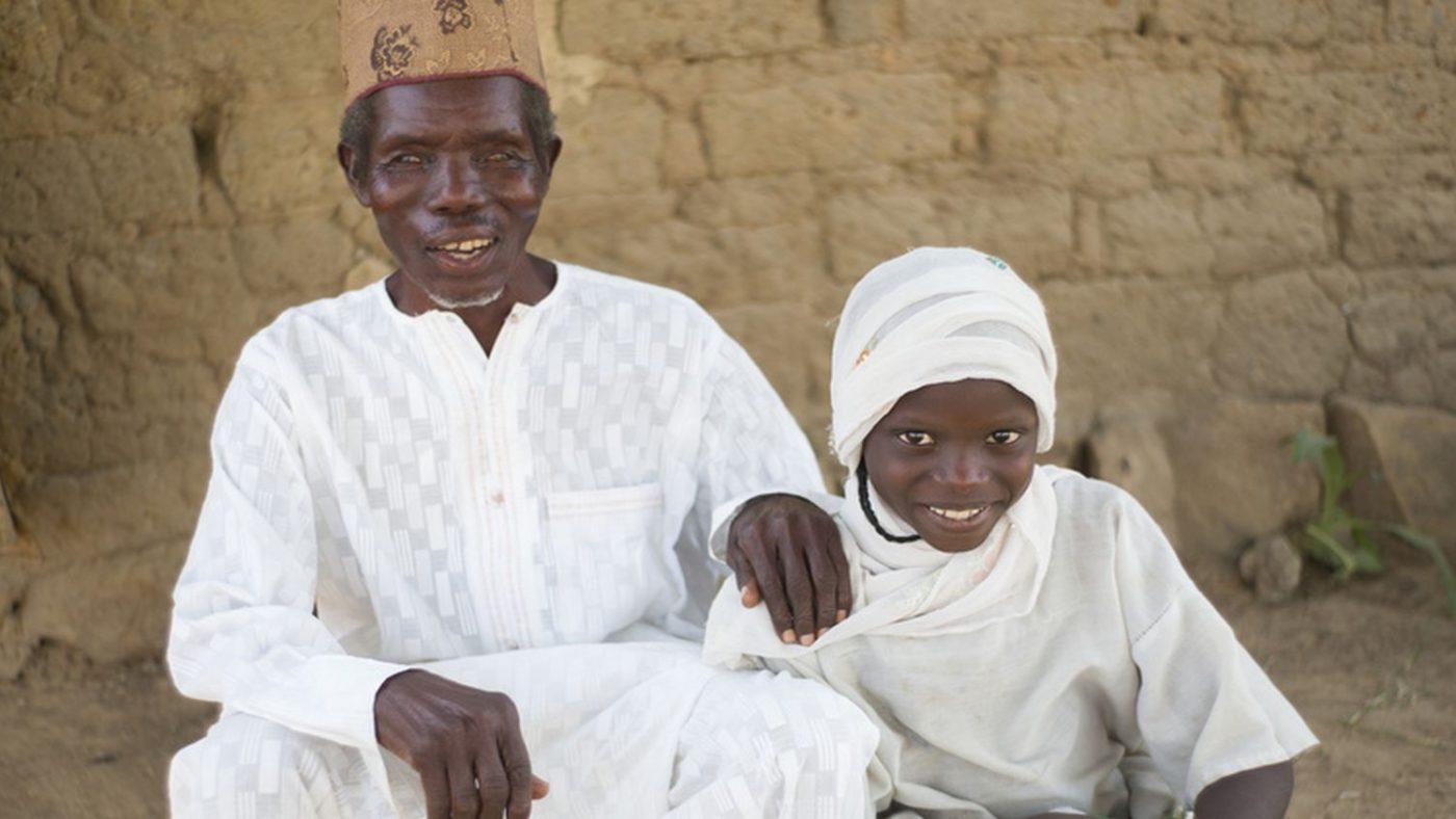 Un uomo anziano e cieco è seduto alla destra di sua nipote e stanno sorridendo