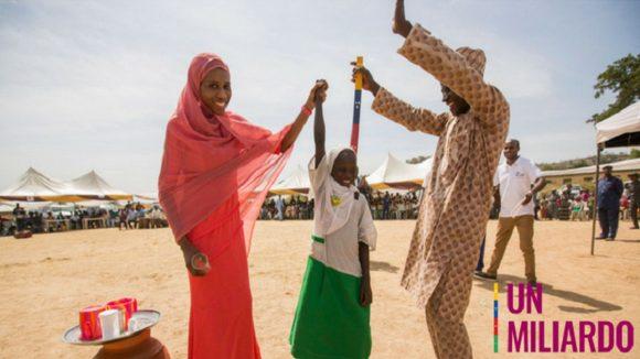 una ragazzina si tiene in mezzo a una donna a sinistra e un uomo a sinistra, lei solleva il braccio della ragazza e lui mantiene il bastone colorato che serve a determinare la dosi giusta di medicine, stanno sorridendo in una piazza del villaggio.