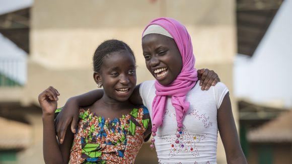 Due bambine sorridenti si abbracciano