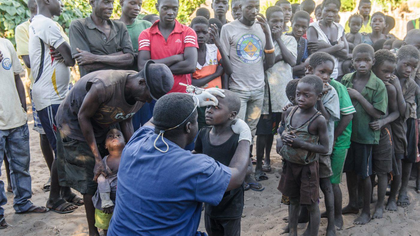 Un dottore sta visitando un bambino e dietro di lui altri bambini aspettano.