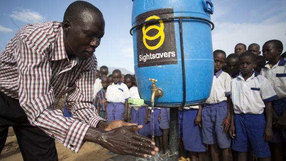 Un uomo mostra ai dei bambini dietro di lui come lavarsi le mani. L'acqua arriva da una tanica con il loro di Sightsavers.