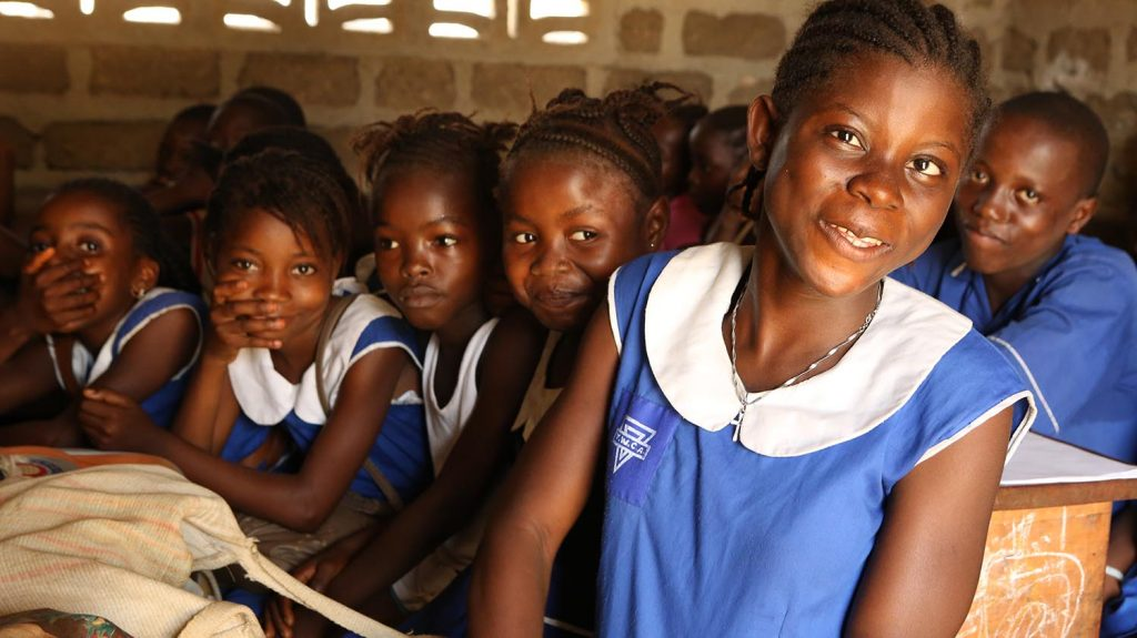 Un gruppo di ragazzine sorridenti a scuola guardano la fotocamera.