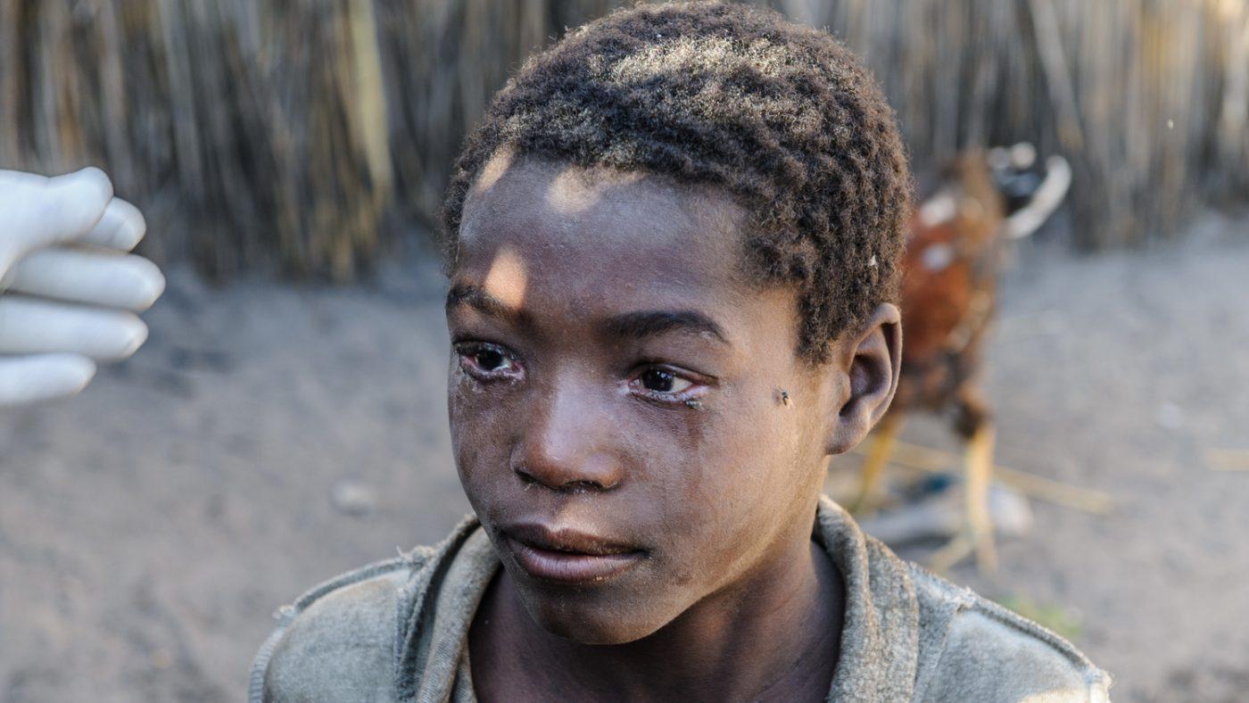 Una ragazzina guarda davanti a sè con gli occhi gonfi di lacrime.