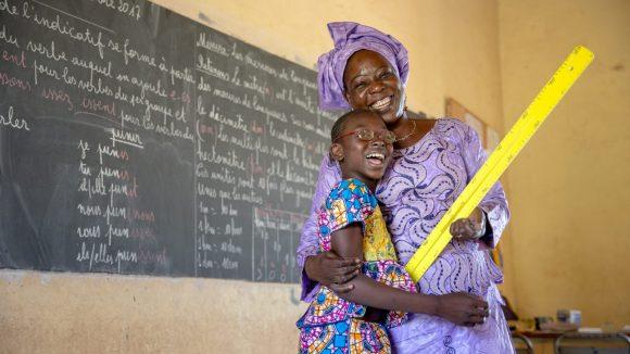 Un'insegnante vestita di lilla abbraccia una giovane studentessa. Entrambe sorridono e alle loro spalle c'è una lavagna.