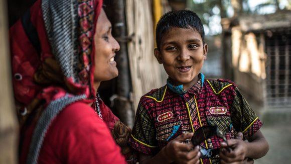 Un bambino e una donna sorridono insieme.