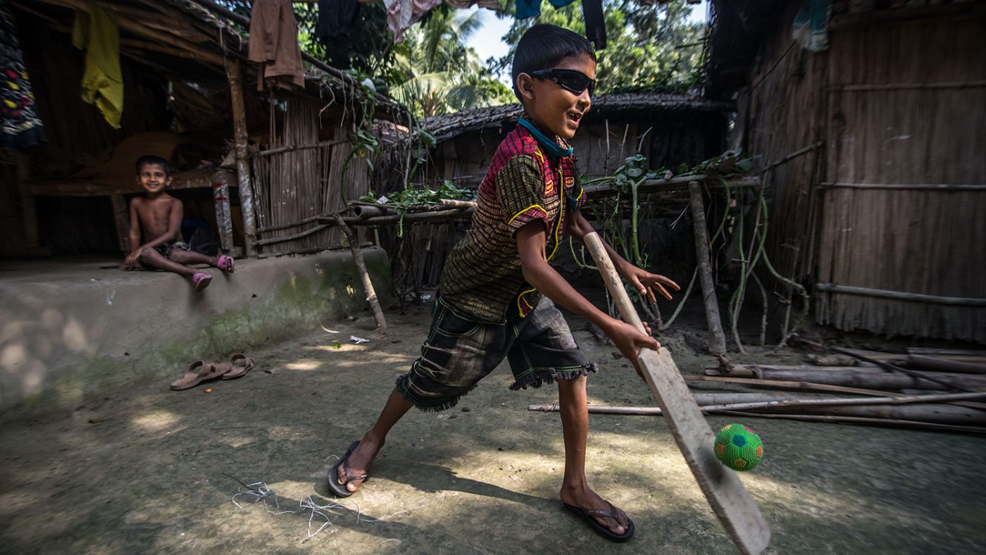 Un bambino con gli occhiali da sole sta giocando a cricket.