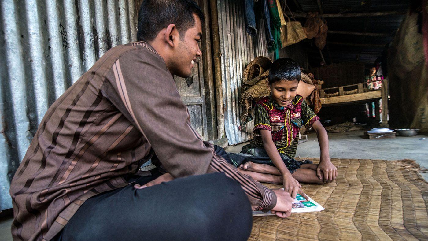 Un uomo sta insegnando a leggere ad un bambino.