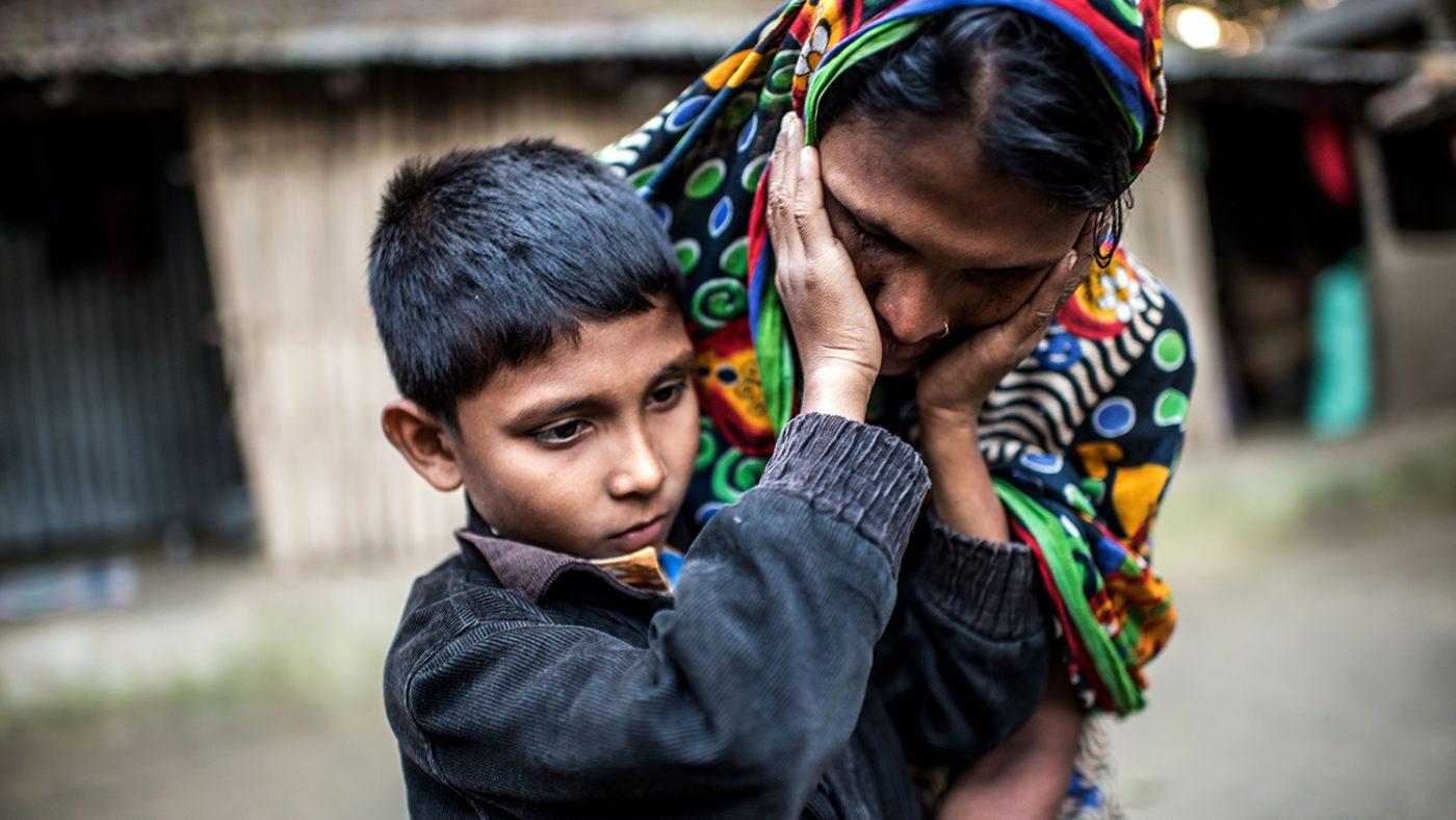 Un bambino guarda nel vuoto mentre sta toccando il viso di una donna che si tiene dietro di lui.