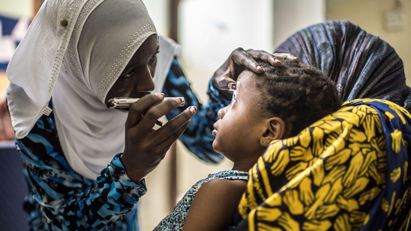 Una bambina seduta si fa visitare gli occhi da un infermiera.