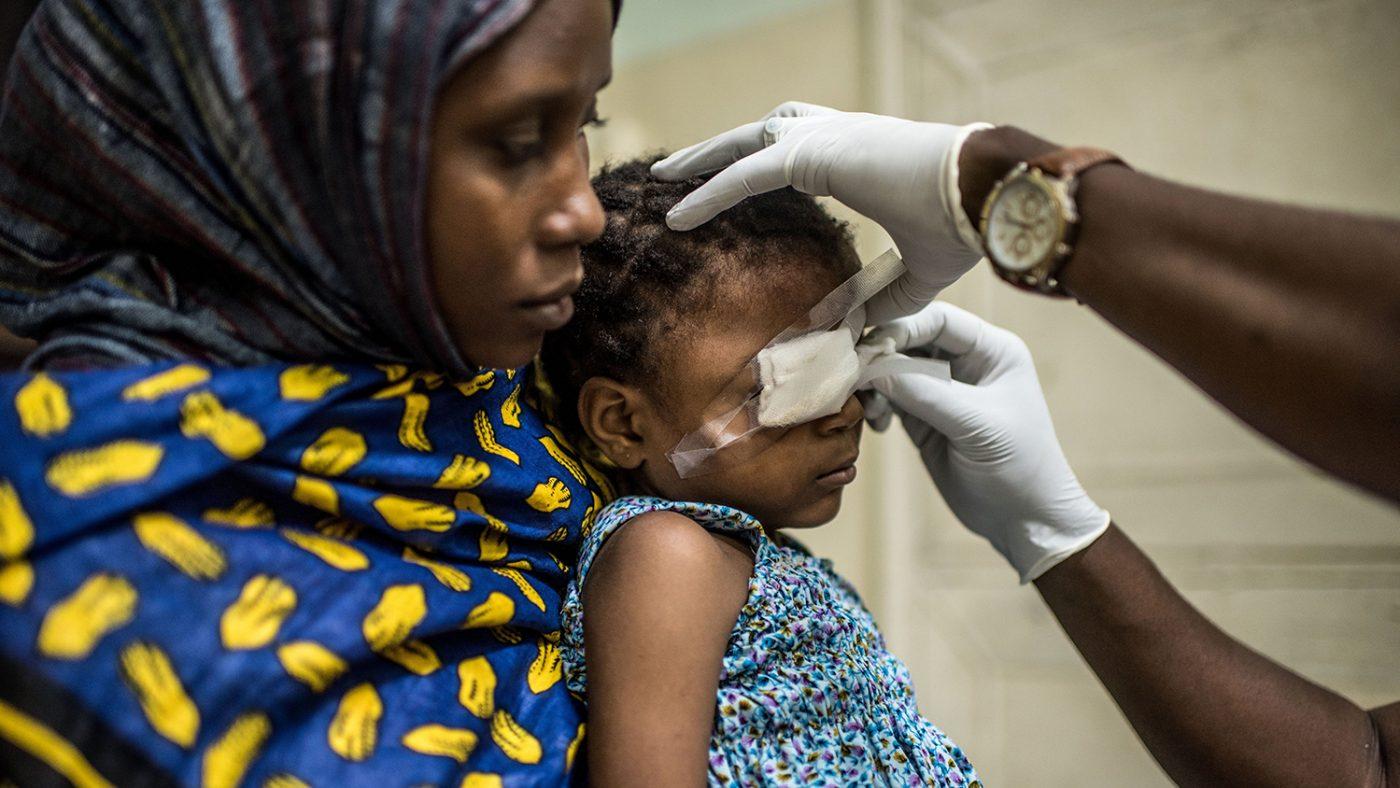 Una bambina si fa togliere le bende dal chirurgo dopo l'operazione sitiene tra le braccia di sua mamma.