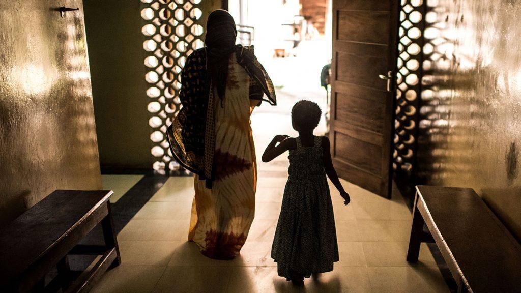 Una bambina e una donna camminano verso l'uscita a contro luce.