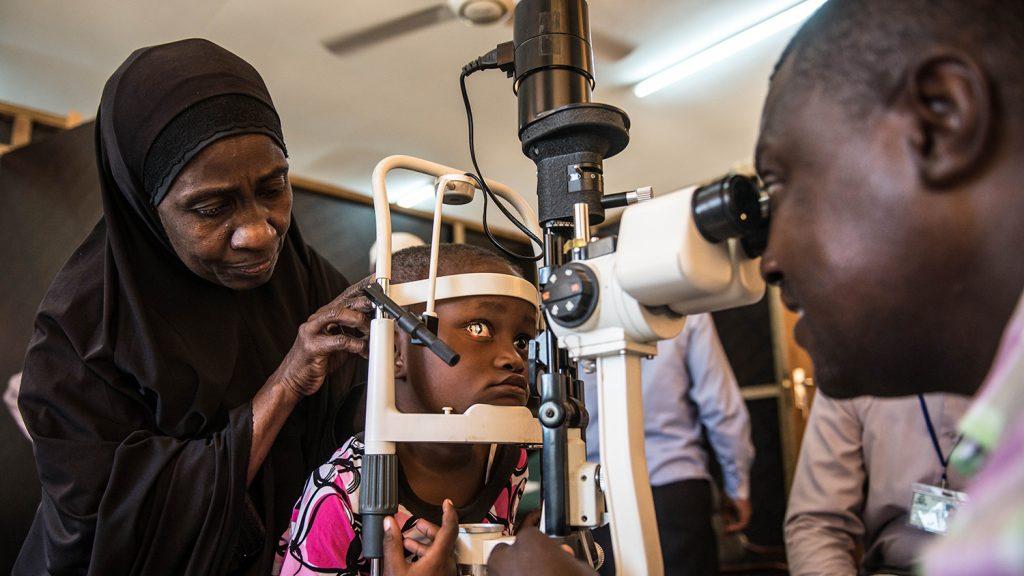 Una bambina guarda dentro ad un apparecchio per l'esame degli occhi.