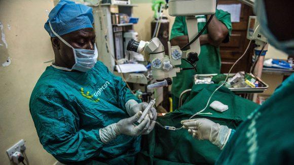 Un uomo sta operando una persona in una sala operatoria.