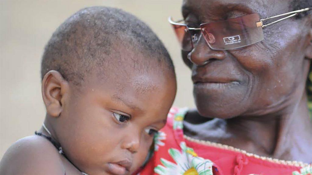 Una donna anziana con indosso occhiali da sole guarda dolcemente un bambino in primo piano.