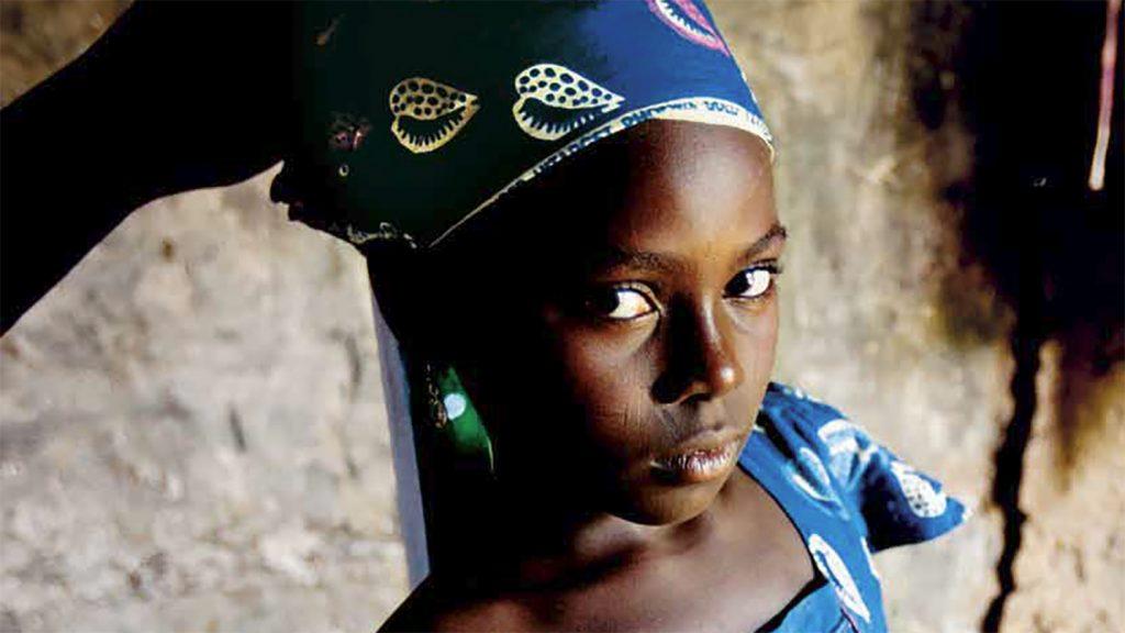 Una ragazzina con un abito e un cappellino blu guarda verso la fotocamera.