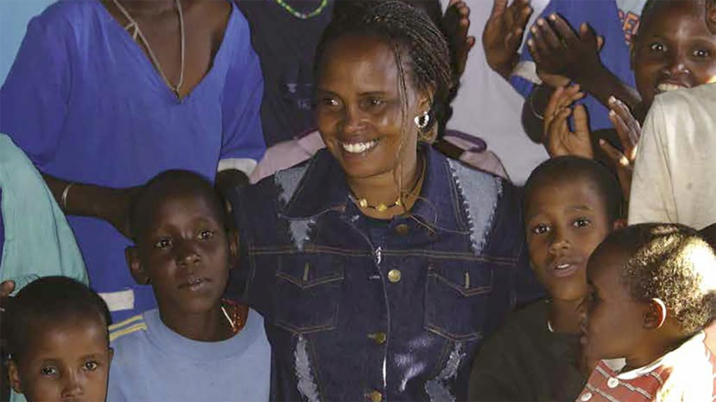 Una donna cieca in mezzo ad un gruppo di ragazzini e li abbraccia.