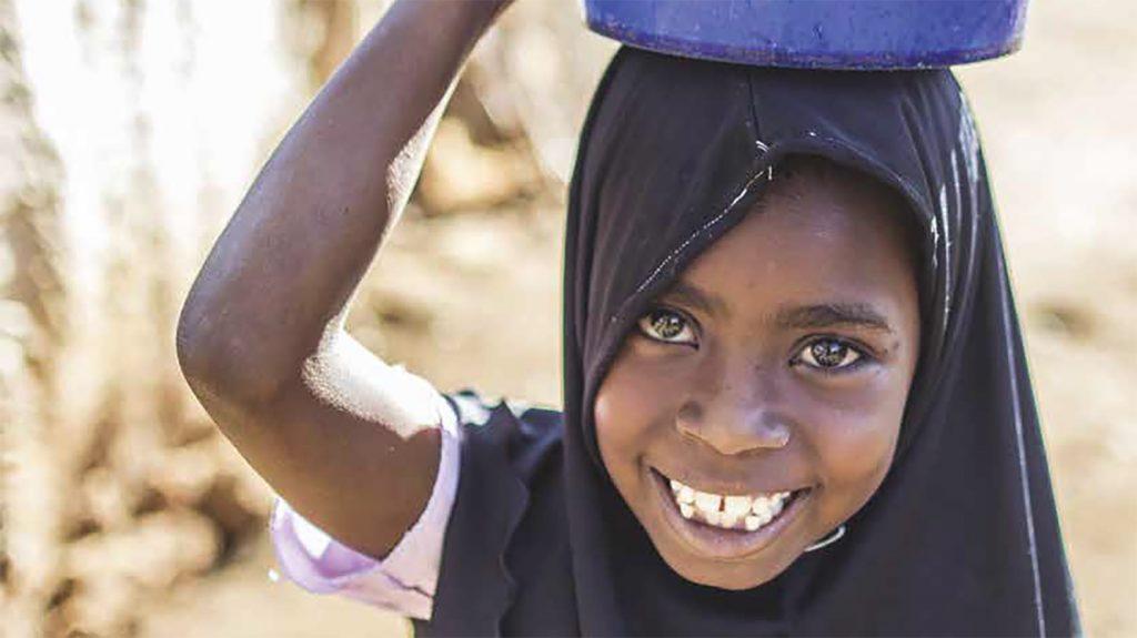 Una bambina sorride davanti a sè e porta in testa un recipiente blu.