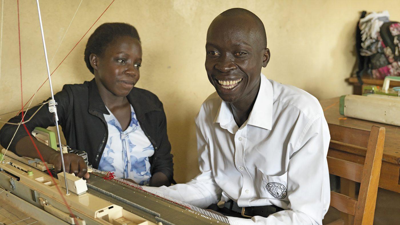 Un uomo cieco sra lavorando a maglia con l'aiuto di un insegnante.