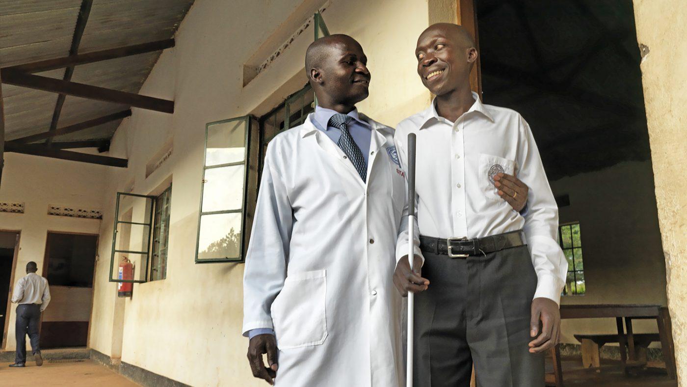 Un chirurgo e un uomo cieco con il bastone per non vedenti stanno sorridendo.
