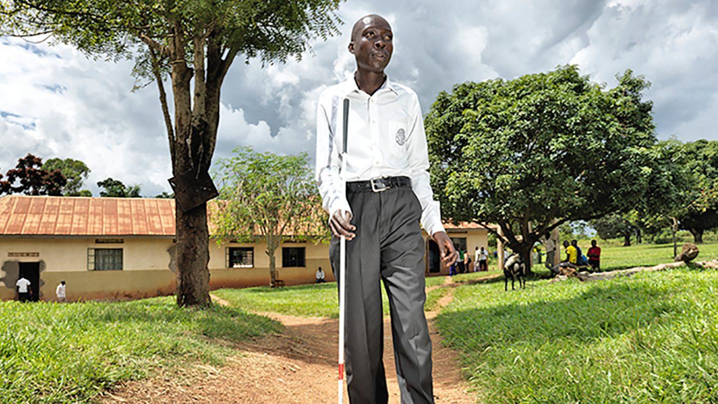 Un uomo si tiene in piedi fuori con l'aiuto di un bastone per non vedenti.