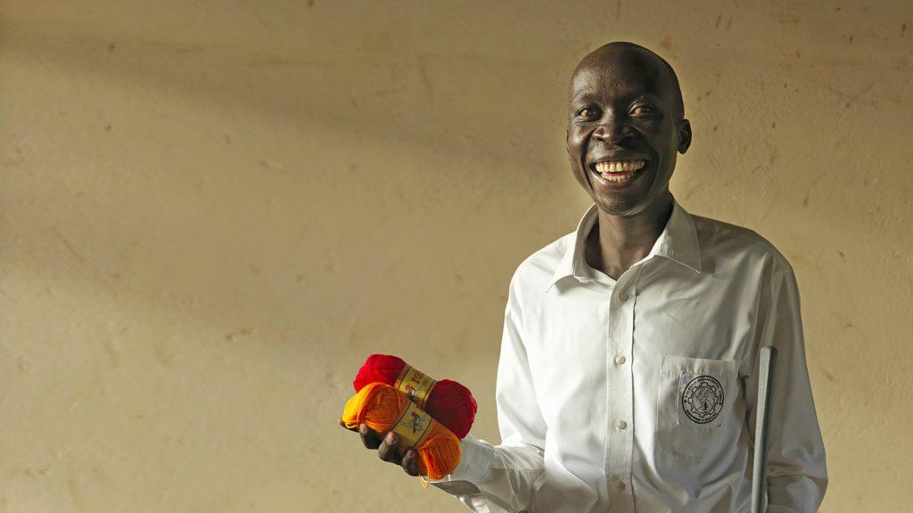Un uomo sta sorridendo e tiene in mano due gomitoli di lana.