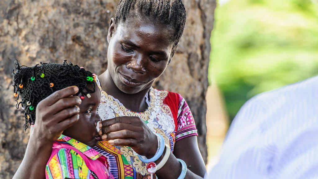 Una donna sta asciugando il naso della sua figlia che tiene in braccio.