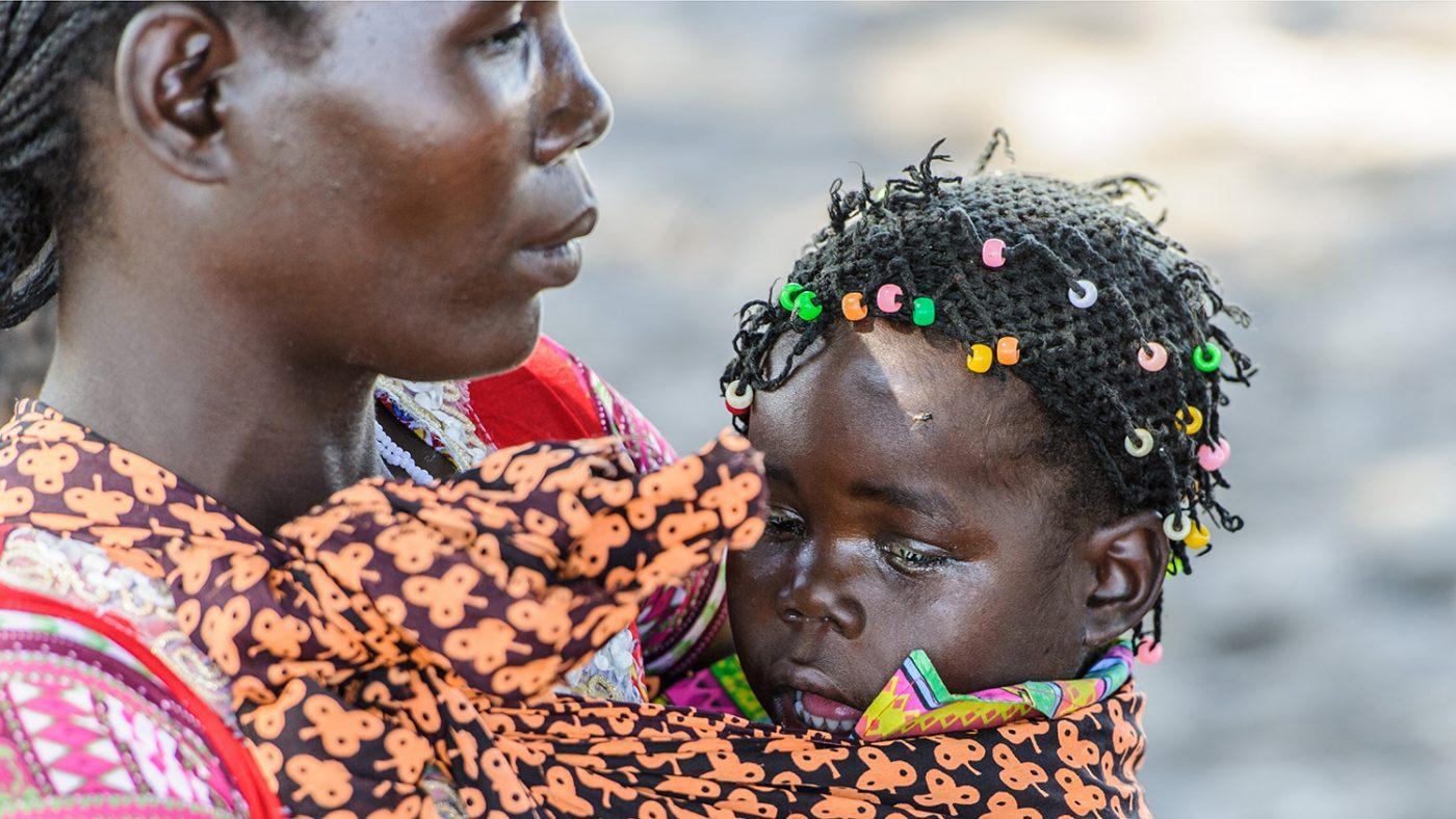 Una bambina a destra è tenuta in braccio dalla sua mamma a sinistra.