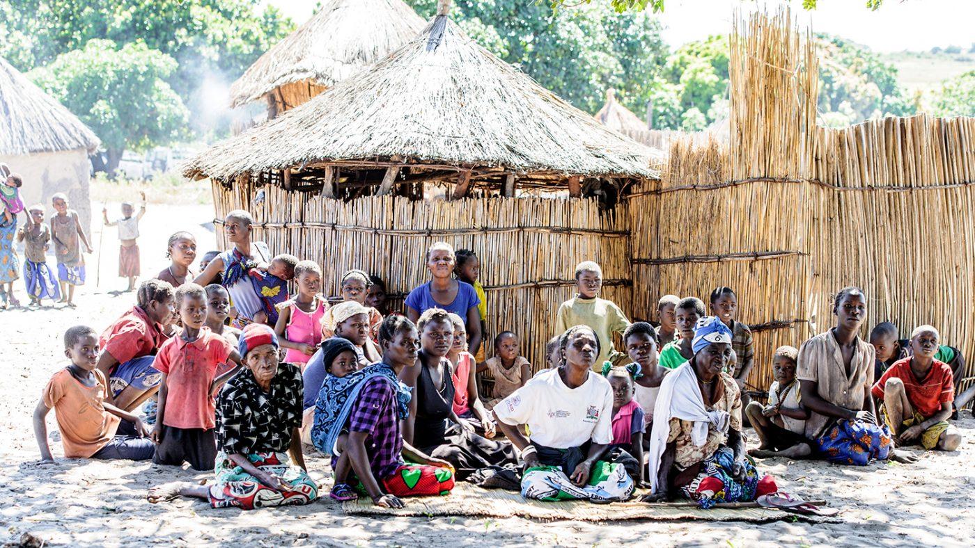 Un gruppo di persone sedute fuori stanno aspettando la visita agli occhi nel villaggio.