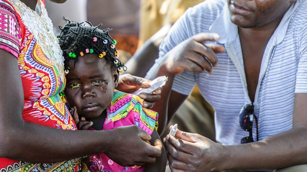 Una bambina tra le braccia della sua mamma sta per ricevere le medicine da un uomo.