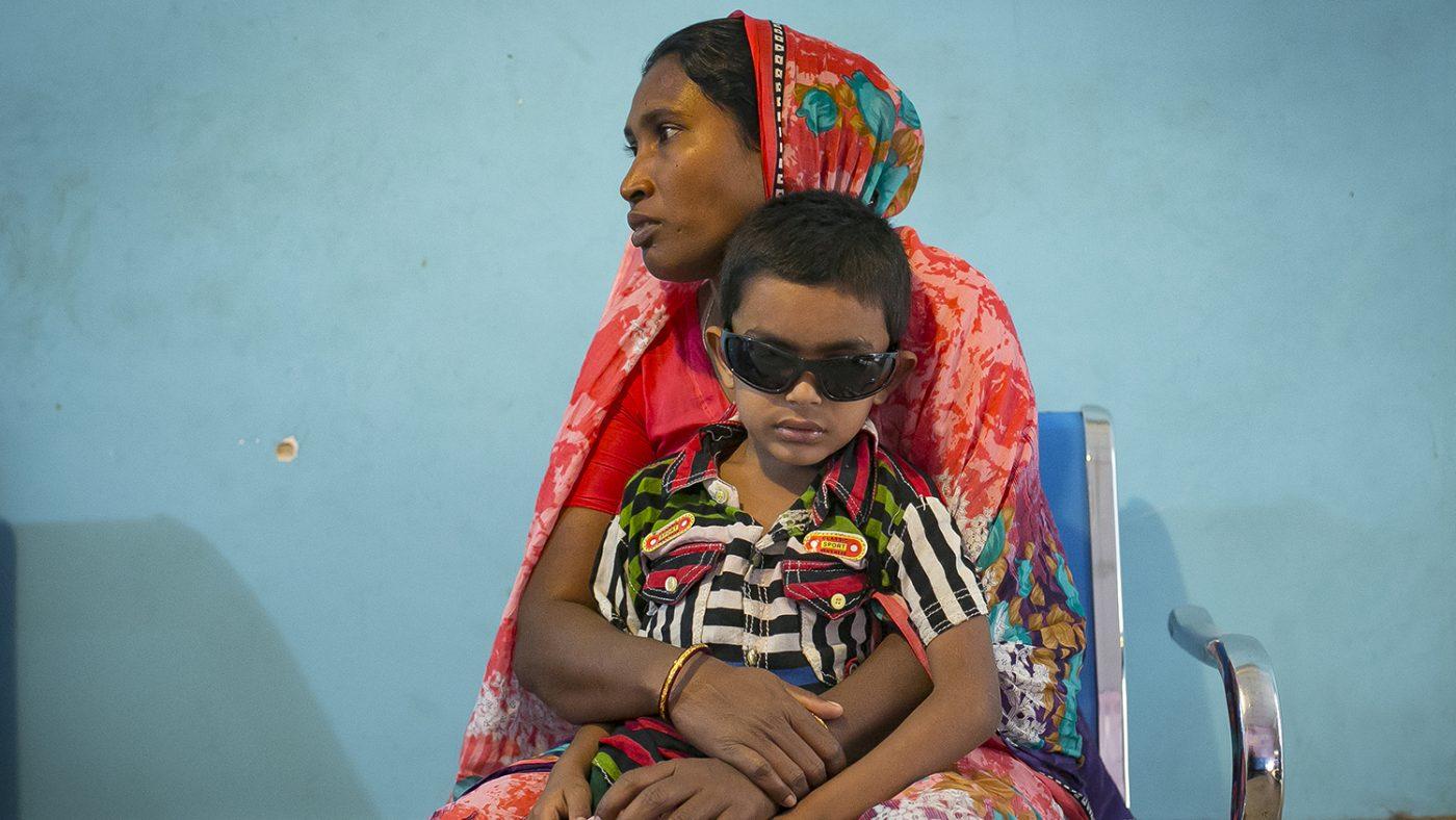 Una mamma seduta tiene in braccio il suo bambino che indossa occhiali da sole.