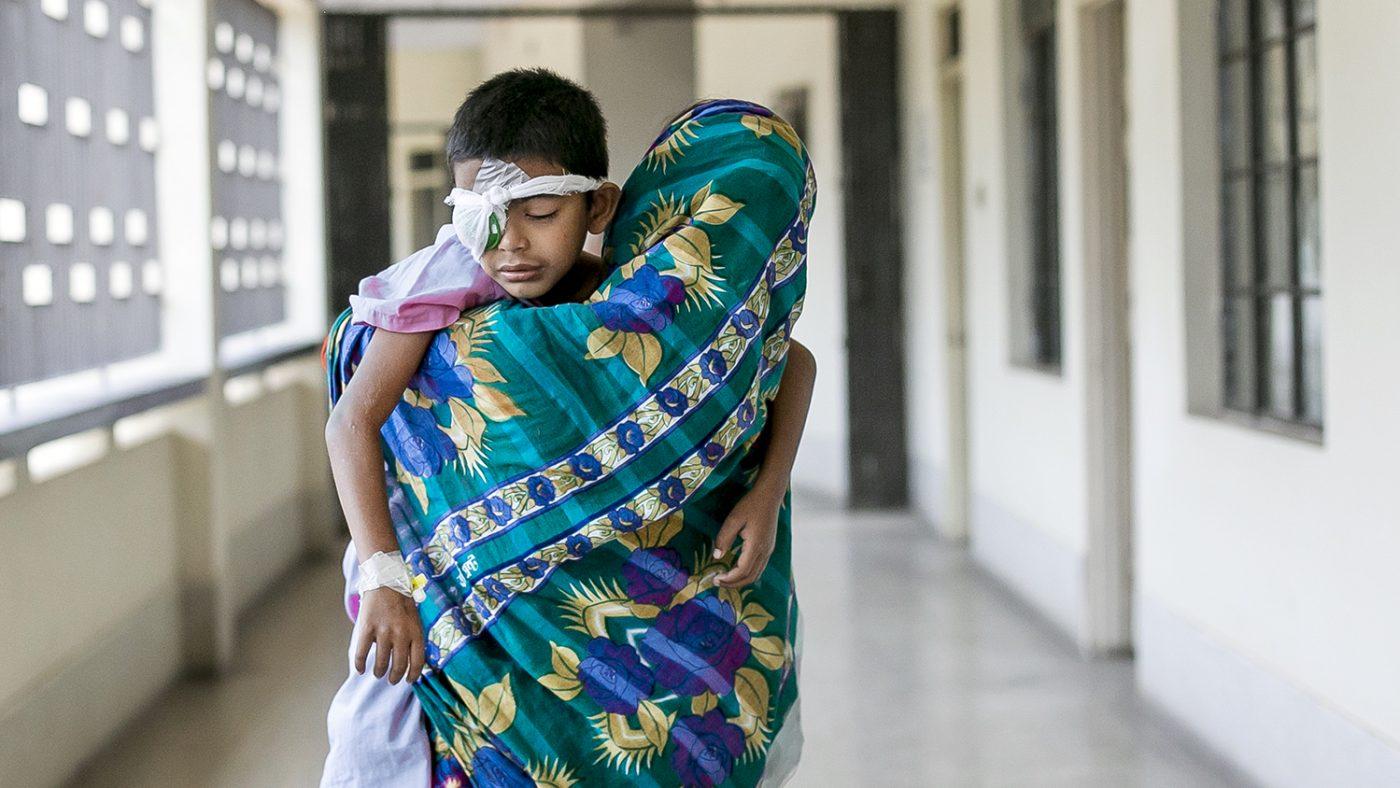 Un bambino con la benda sull'occhio è in braccio alla sua mamma in un corridoio dell'ospedale.