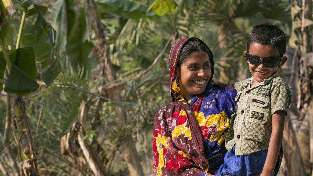 Una donna con il velo e un vestito colorato guarda di lato e sorride.
