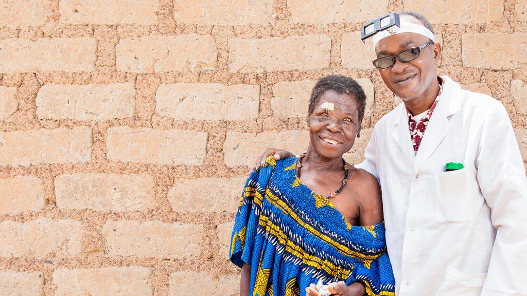 Un dottore sorridente abbraccia una donna appena operata, anche lei sorridente.
