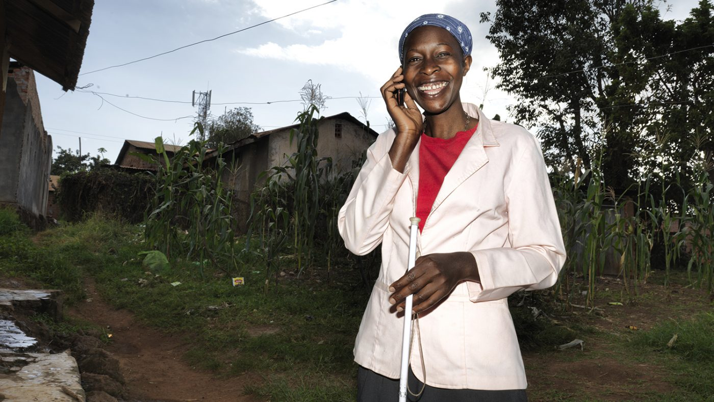 Una donna al cellulare sorride e tiene in mano un bastone bianco.