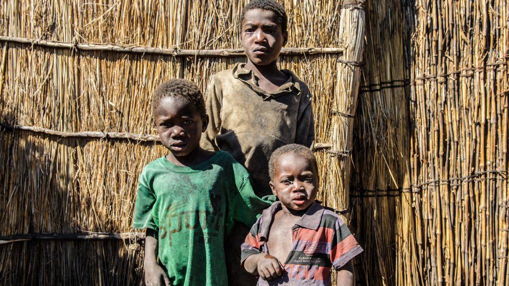 Una ragazzina e due bambini sono in piedi davanti ad una capanna con le facce sporche e sofferenti.