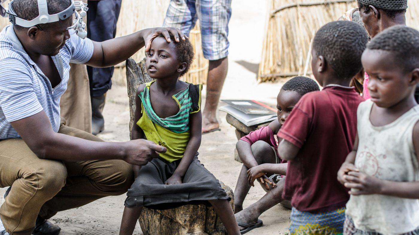 Un dottore posa la mano sulla testa di una bambina e visita i suoi occhi.