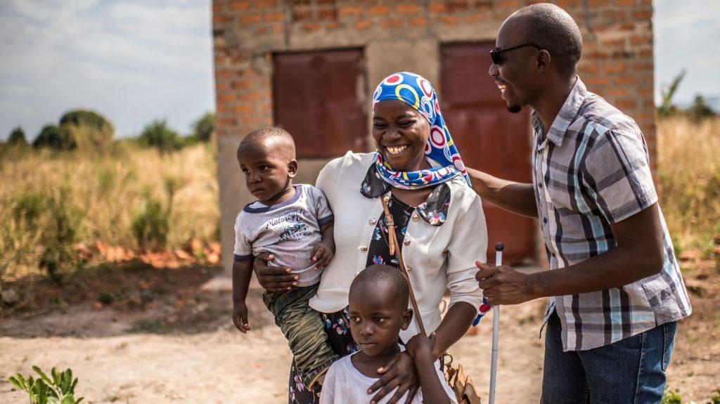 Un uomo cieco con il bastone e gli occhiali e una donna abbracciano i propri figli sorridendo.