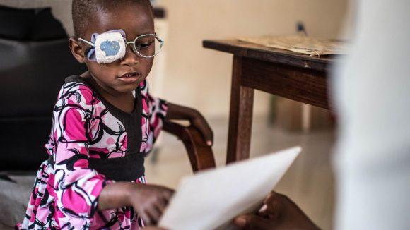 Una bambina con la benda sull'occhio e con indosso un paio di occhiali indica un foglio per provare a leggere