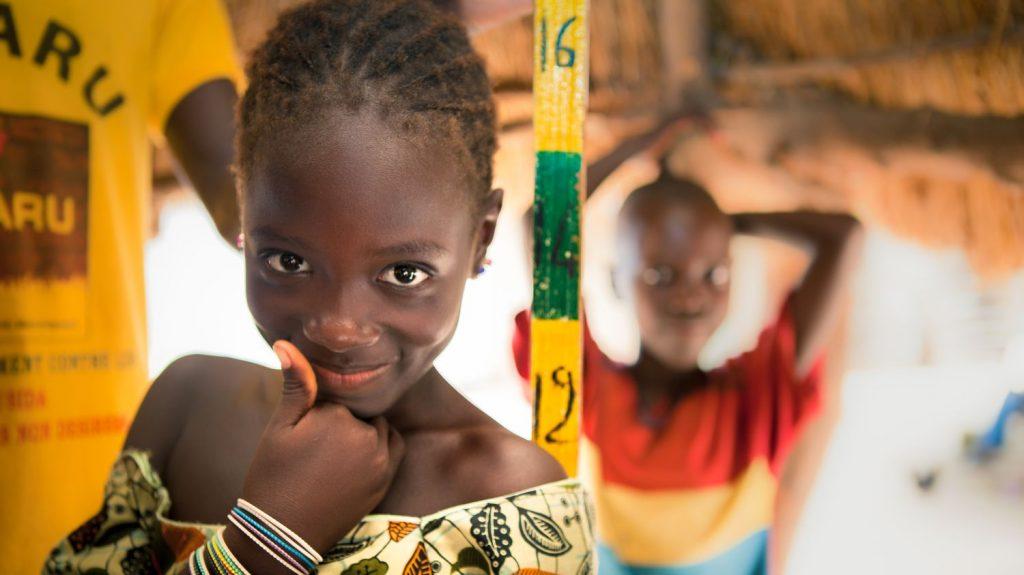 Una bambina sorride e alle sue spalle il bastone della misurazione.