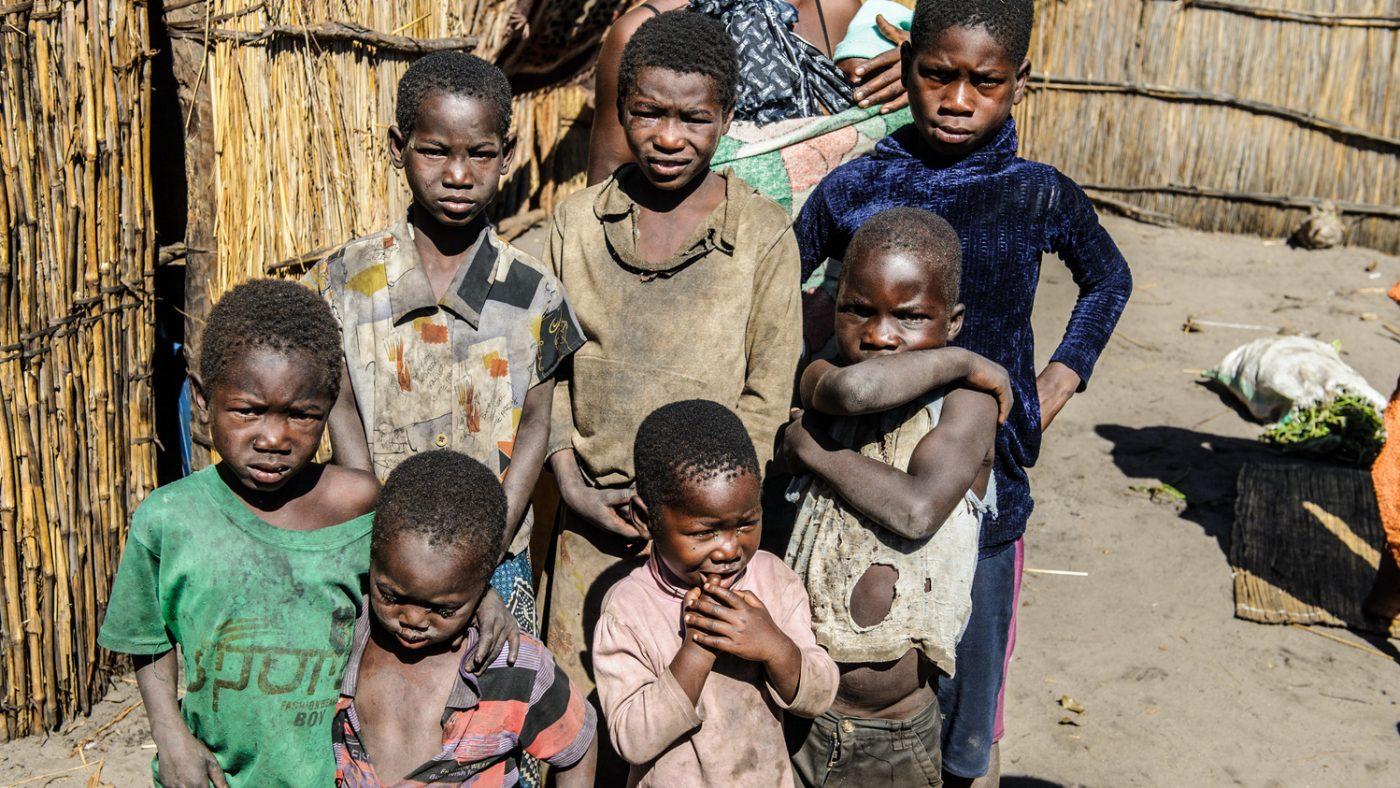 Tanti bambini in piedi con l'aria sofferente.