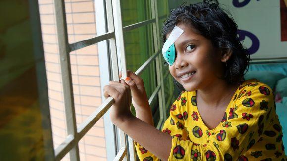 Una bambina con la benda sull'occhio sorride.