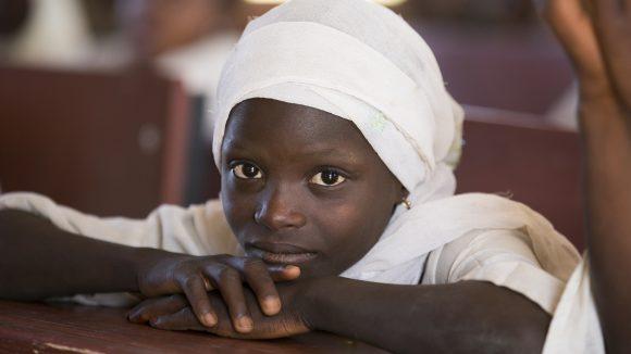 Una bambina con il velo bianco appoggiata su un banco.