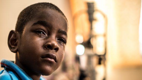 Un bambino triste in primo piano guarda davanti a sè e ha il viso rigato di lacrime.