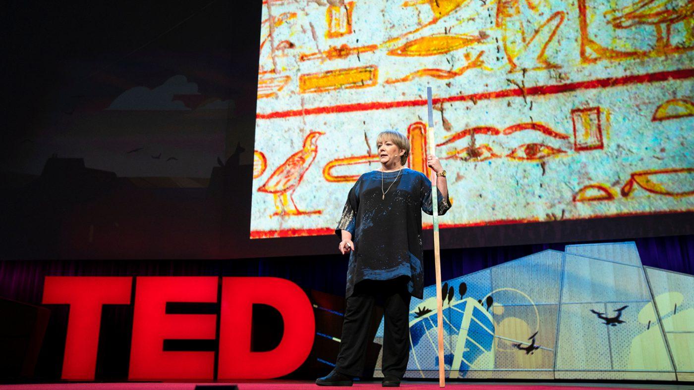Una donna sta parlando sul palcoscenico del TED e tiene in mano un lungo bastone.