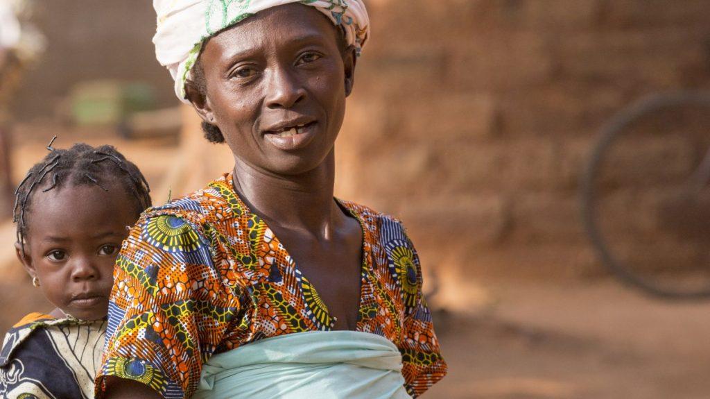 Una mamma porta il suo bambino avvolto in una fascia.