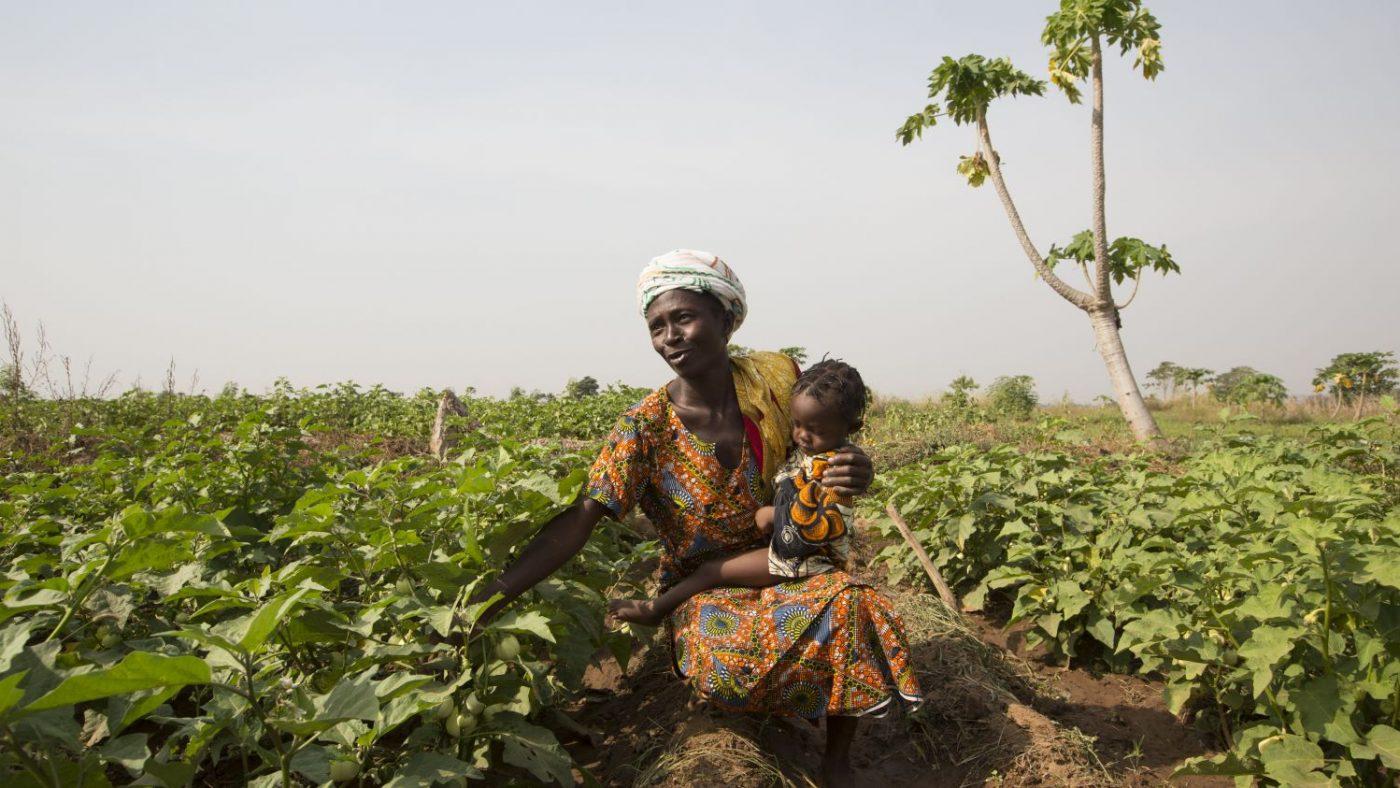 Una mamma con in braccio una bimba è chinata sui campi di lavoro