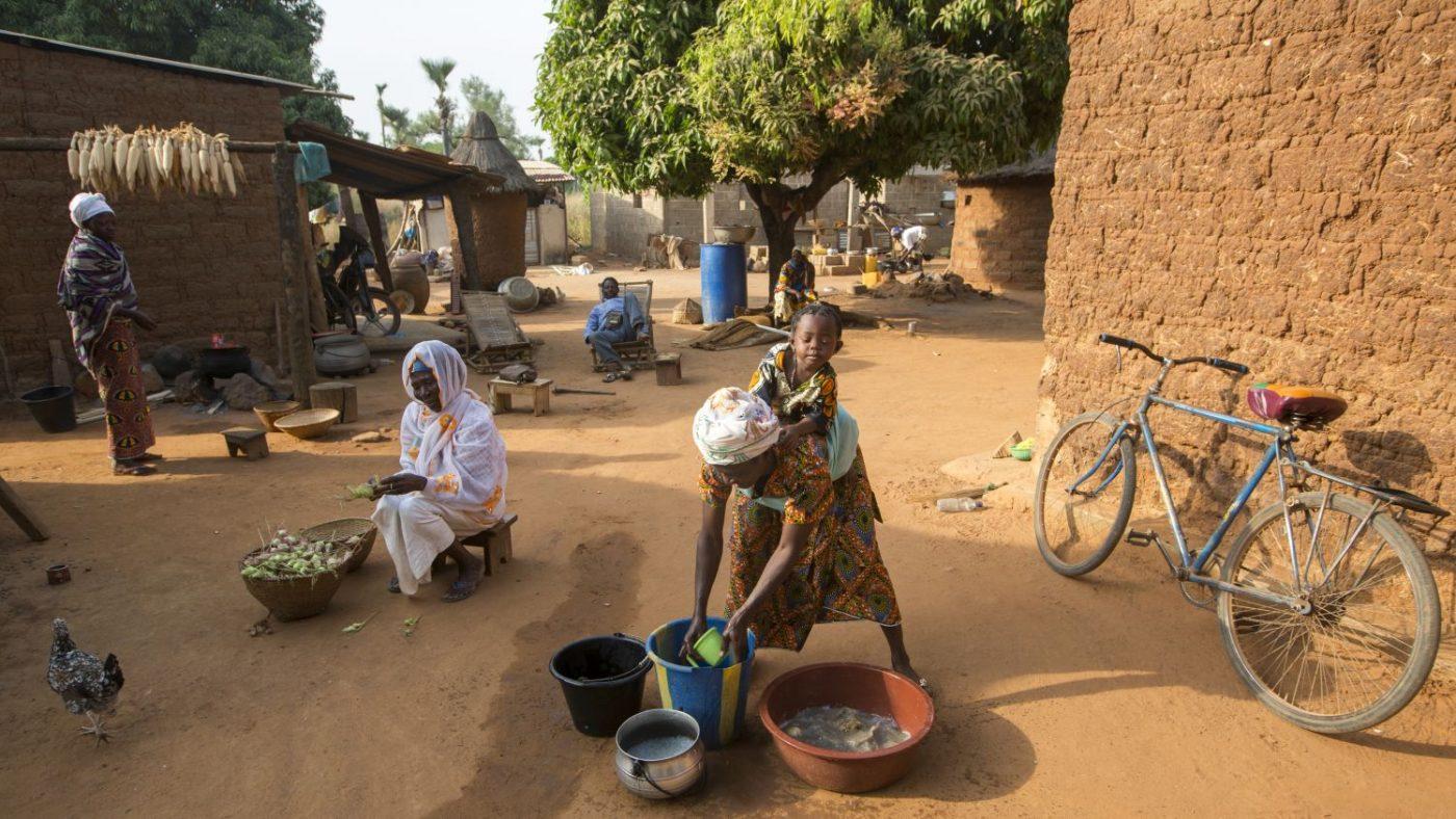 Una donna con una bambina sulla schena è china su un secchio di acqua.